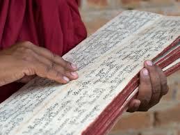 Tibetan monk with sacred Buddhist text