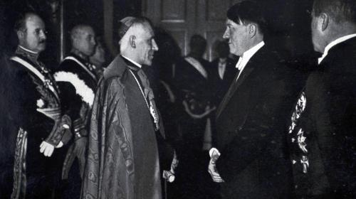 "Adolf Hitler with Vatican ambassador Cesare Orsenigo in 1935. Orsenigo believed in the Italian fascist ideal and hoped the German variety would develop into something similar. He was a controversial figure among his contemporaries and remains the subject of historical criticism for his advocacy of ""compromise and conciliation"" with the Nazis, particularly in relation to The Holocaust. Pope Pius XII has been criticized by several contemporaries and historians for not replacing Orsenigo as nuncio to Germany."